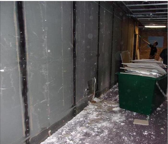 demolition ongoing with waster in a small green dumpster and plastic sheeting on the walls