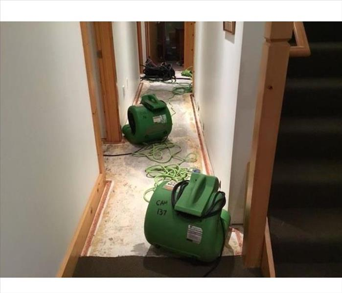 Hallways with exposed subfloor and SERVPRO drying equipment
