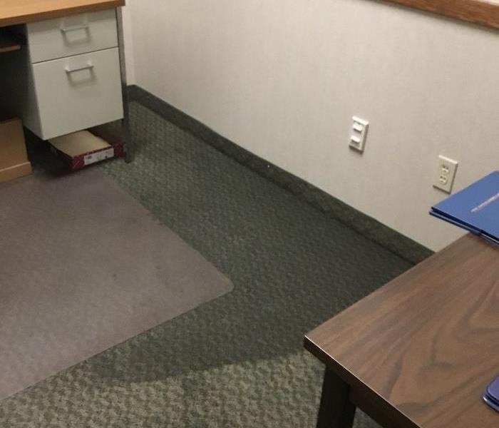 Office with desks with commercial water damage on the carpet