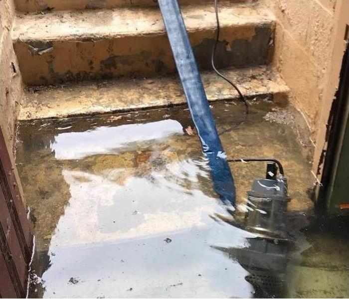 A submersible pump, blue hose, extracting water from a cellar exterior entrance