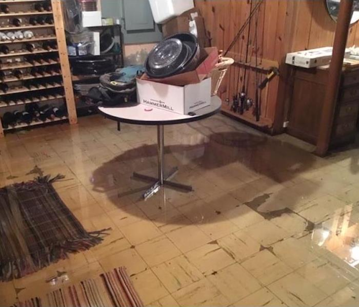 basement with standing water and items stacked on a table