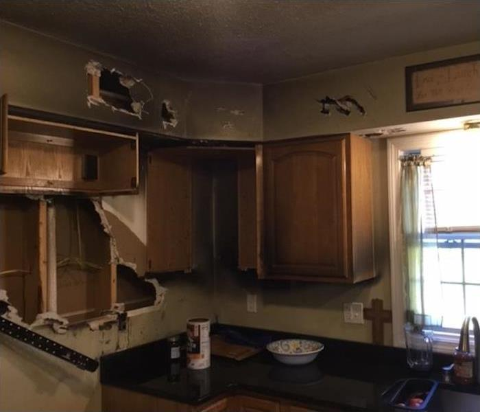 kitchen with fire damage and torn out cabinets